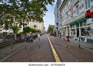Karlsruhe, Baden-Wuerttemberg / Germany - August 9, 2019: Pedestrian street in Karlsruhe with typical shops and the Karlsruhe Palace in the background
