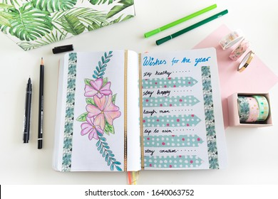 Karlsruhe, Germany - 02.02.2020: bullet journal - close up of wishes for the year page with beautiful hand drawn flowers decorated with fine liners, washi tape and jungle patterned directory