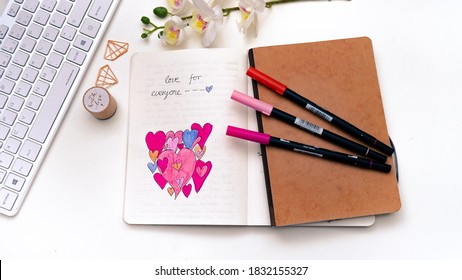 Karlsruhe, Germany - 02.02.2020: bullet journal - close up of  handdrawn hearts in notebook with fine liners, keyboard on white  background