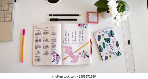 Karlsruhe, Germany - 11.11.2019: Journal life style, Bullet Journal - Planer - Notebook - top view with utensils arranged on white background, orchid, pencils, sticky notes