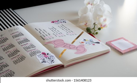 Karlsruhe, Germany - 11.11.2019: Journaling life style, Bullet Journal - Planer - Notebook - diagonal top view isolated on white background with orchid