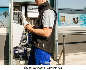 KARLSRUHE, GERMANY - MAY 11, 2018: Side view of male service operator repairing the train ticket fahrkarte service vending machine located near the entrance of the Karlsruhe Airport