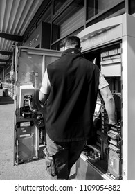 KARLSRUHE, GERMANY - MAY 11, 2018: male service operator repairing the train ticket fahrkarte service vending machine located near the entrance of the Karlsruhe Airport - black and white