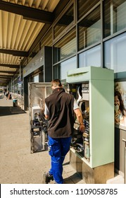KARLSRUHE, GERMANY - MAY 11, 2018: Rear view of male service operator repairing the train ticket fahrkarte service vending machine located near the entrance of the Karlsruhe Airport
