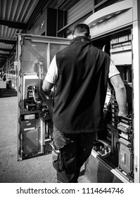 KARLSRUHE, GERMANY - MAY 11, 2018: Man service operator repairing the train ticket fahrkarte service vending machine located near the entrance of the Karlsruhe Airport - black and white