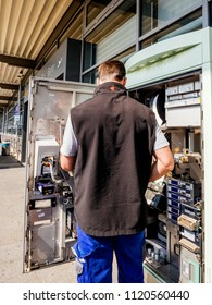 KARLSRUHE, GERMANY - MAY 11, 2018: German male service operator repairing the train ticket fahrkarte service vending machine located near the entrance of the Karlsruhe Airport