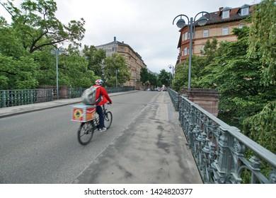 Karlsruhe, Germany, May 2015: Pizza courier on the bike Hirschbrücke / Karlsruhe