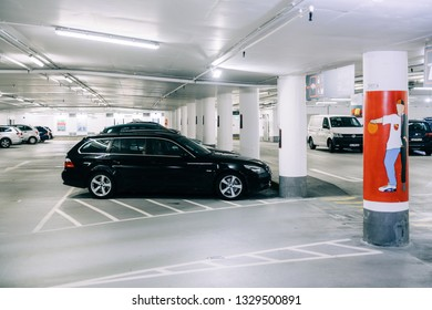 Karlsruhe, Germany - Oct 29, 2017: New modern underground parking in Schlossplatz neutral colored parking with multiple cars parked and female dedicated area for park