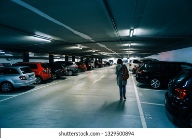 Karlsruhe, Germany - Oct 29, 2017: Rear view of German woman walking toward car in new underground parking in Schlossplatz blue tone colored parking with multiple cars parked and female dedicated area