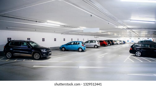 Karlsruhe, Germany - Oct 29, 2017: New underground parking in Schlossplatz neutral tone colored parking with multiple cars parked and female dedicated area for park