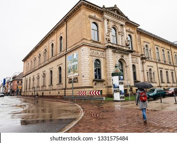 Karlsruhe, Germany - Oct 29, 2017: German city of Karlsruhe with young woman with umbrella walking toward Staatliche Kunsthalle Karlsruhe State Art Gallery
