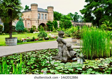 KARLSRUHE, GERMANY-JULY 2013: Botanical gardens (Botanischer Garten Karlsruhe) with old gate building, palace grounds, lily pond, and statue of two cherubs playing with a carp in the water.