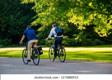 Karlsruhe/Germany - July 19 2018: Two men are taking the bike to ride to the office to start their working day instead of taking the car or the subway. Concept of a healthy lifestyle