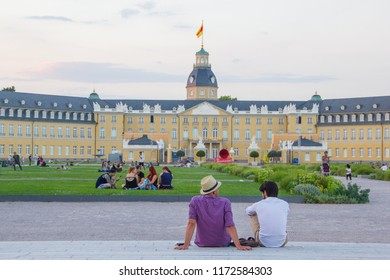Karlsruhe/Germany - July 2018: People are relaxing in front of the castle called Schloss Karlsuhe to spend their leisure time there as a central meeting point to relax and take a walk