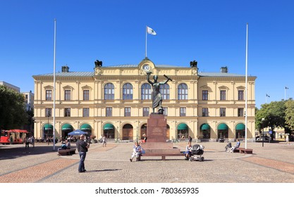 Karlstad, Sweden - August 15, 2013: View of the main square with people and the old town hall behind the peace monument Freden during a sunny day with clear blue sky.