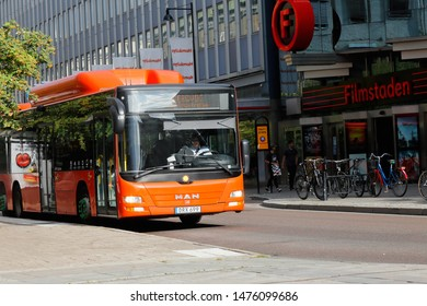 Karlstad, Sweden - August 7, 2019: A orange colored city bus in use for public transportation at Drottningatan street in downtown Karlstad.