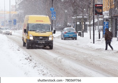 Karlstad, Sweden - January 30, 2014: A yellow DHL parcel delivery van driving on the street Ostra Torgatan with winter road conditions in the city center during a snowfall.