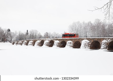 Karlstad, Sweden - January 31, 2019: One red public transport buss on the old stone arch bridge crossing the river Klaralven.