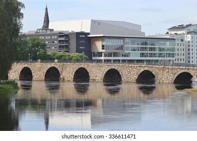 KARLSTAD, SWEDEN - JULY 30, 2015: The Ostra Bron, or Eastern bridge, in Karlstad, Sweden. It is Swedens longest arched stone bridge. In the Background the cathedral of Karlstad, Domkyrka.