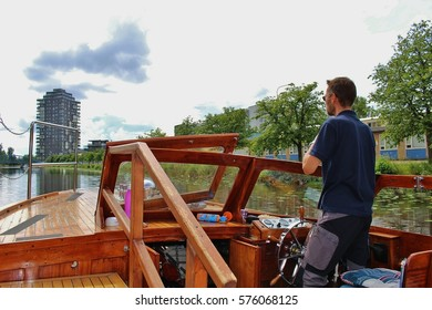 Karlstad, Sweden - July 30, 2015: On board of a waterbus in Karlstad, Sweden, Europe. Driver on the steering wheel. The boats drive on canals and the bay of the town and cost as low as normal buses.