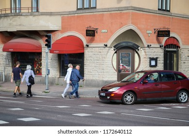 KARLSTAD, SWEDEN - SEPTEMBER 1, 2018: Car waiting for people to pass the crosswalk on Hamngatan in Karlstad city centre, Sweden