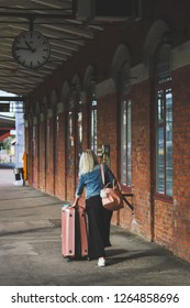 KARLSTAD, SWEDEN - SEPTEMBER 1, 2018: Woman with heavy luggage the platform at the railway station in Karlstad, Sweden