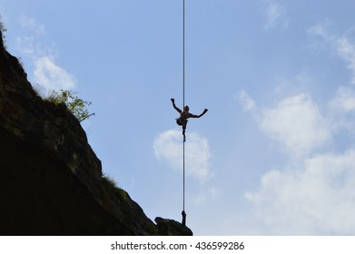 Karlukovo, Bulgaria - June 12, 2016: Silhouette of young highline walker high on a tightrope in Prohodna Cave