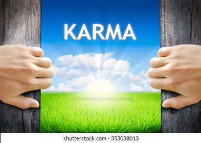 "KARMA. Hand opening an old wooden door and found wording ""KARMA"" over green field and bright blue Sky Sunrise."