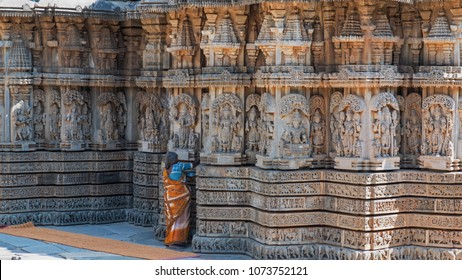 Karnataka, India - March 2, 2018: Unidentified female attendant brushing dust from crevices in the intricately carved soapstone walls of the 13th century Channakeshava temple at Somnathpur
