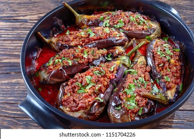 Karniyarik - Stuffed Eggplants, Aubergines with ground beef and vegetables baked with tomato sauce in a baking dish, turkish cuisine, horizontal view from above, close-up