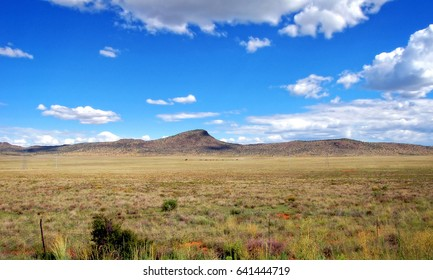 Karoo in South Africa. Scenic view of semi-desert. Beautiful landscape of unique African Great Karoo. Amazing semi desert with sparse vegetation with hills, blue sky and clouds in the background.