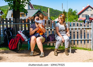Karpacz, Poland - May 7, 2018: Women with baby boy sitting on a wooden bench of a park on a sunny day