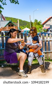 Karpacz, Poland - May 7, 2018: Two women feeding a baby boy on a wooden bench at a park