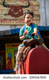 Karpacz, Poland - May 8, 2018: Young boy with a biscuit sitting on a ride attraction at the Western City