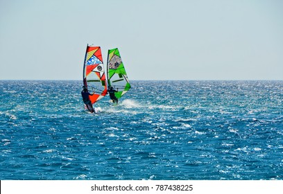 Karpathos island Dodecanese, Greece. August 1, 2014. Seascape with windsurfers on wet suits and their colorful windsurfing boards on the blue waters and the bright sunshine of the Aegean Sea.