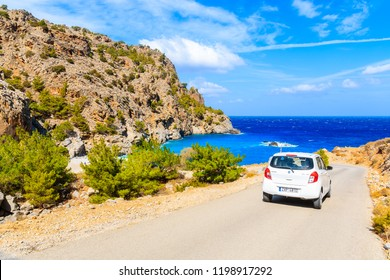 KARPATHOS ISLAND, GREECE - SEP 26, 2018: Rental car driving on mountain road to beautiful Achata beach on sunny summer hot day, Karpathos island, Greece.