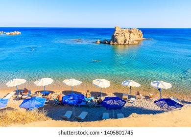 KARPATHOS ISLAND, GREECE - SEP 26, 2018: People relaxing on beautiful beach on Karpathos island near Ammopi village, Greece.