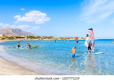 KARPATHOS ISLAND, GREECE - SEP 29, 2018: Instrctor teaching windsurinf sport on sea in beautiful bay with beach, Karpathos island, Greece.