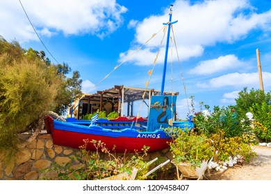 KARPATHOS ISLAND, GREECE - SEP 30, 2018: Fishing boat in front of taverna in Finiki port on Karpathos island, Greece.