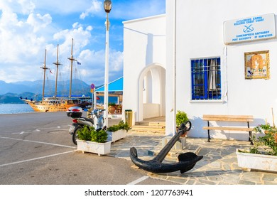 KARPATHOS PORT, GREECE - OCT 1, 2018: White buildings in Pigadia fishing harbour on Karpathos island at sunset time, Greece.