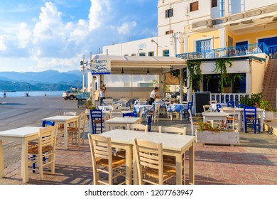 KARPATHOS PORT, GREECE - OCT 1, 2018: Waiter preparing tables in Pigadia fishing harbour taverna on Karpathos island at sunset time, Greece.
