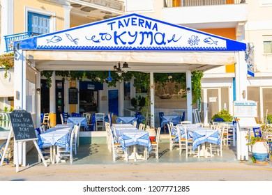 KARPATHOS PORT, GREECE - OCT 1, 2018: Tables in Pigadia fishing harbour taverna on Karpathos island at sunset time, Greece.