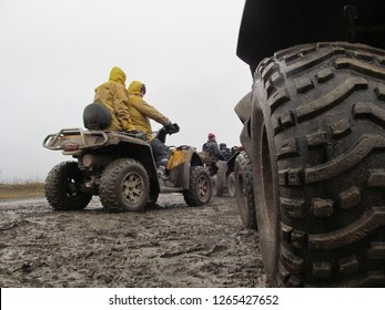 Karpaty, Ukraine - January 2018: A man rides an ATV off-road. Dirty quad bike during a trip along the forest road. A company of young people is actively resting in the mountains.