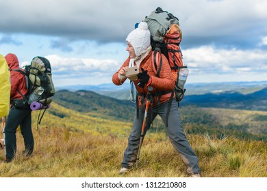 Karpaty, Ukraine- September 29, 2018: A girl with a backpack makes a photo with a mobile phone during a hiking trip.