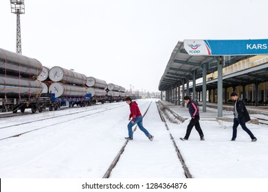 Kars Train Station, Kars/Turkey-01/24/2016: Unknown three young people walking in the train station on a cold winter day.