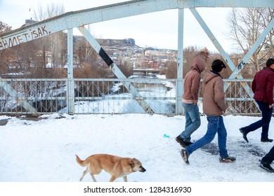 Kars / Turkey - 01/22/2016: Unknown young people are crossing the bridge. Kars, Turkey.
