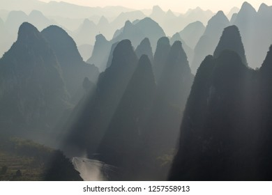 Karst Limestone hills in silhouette at sunrise over Li River as seen from Xianggong Mountain, near Guilin, China. Sun rays shining between hills.
