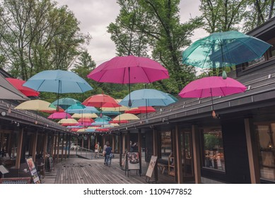 Karuizawa, Japan - 31 May, 2018: People walking in Harunire Terrace, a trendy shopping and dining area built on a wooden terrace surrounded by the forest. Witness the arcade of colourful umbrellas.