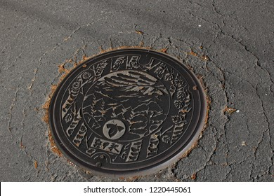 Karuizawa, Japan - October 28, 2018: A cute manhole cover on the floor at Karuizawa. Beautiful landscape is engraved on a metal manhole cover as a symbol for the city of Karuizawa, Japan.