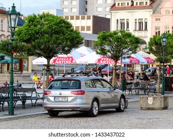 KARVINA, CZECH REPUBLIC - JUNE 1, 2019: Volkswagen Passat Variant car parked in front of a gaden restaurant on the Masarykovo namesti (Masaryk town square) in Karvina with people drinking and relaxing